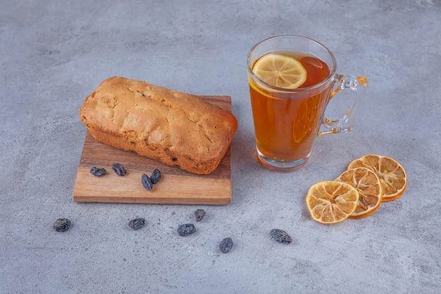 Сладкий торт с изюмом и чашка чая с нарезанным лимоном на мраморной поверхности.