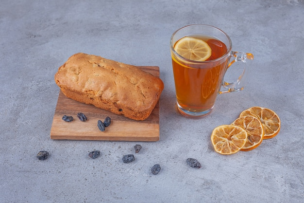 Sweet raisin cake and cup of tea with sliced lemon on marble surface.