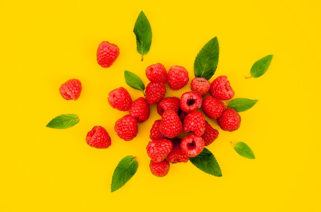 Sweet raspberries with leaves on bright surface