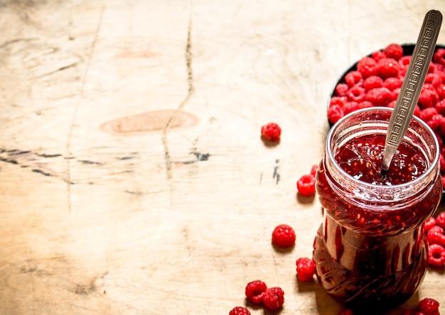 Sweet raspberry jam in jar with spoon.