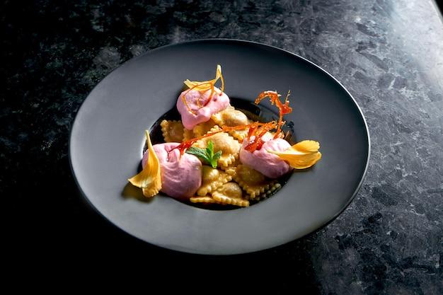 체리와 핑크 아이스크림을 곁들인 달콤한 라비올리는 어두운 대리석 테이블에 검은 접시에 담겨 있습니다. 레스토랑 음식. 이탈리아 요리. 달콤하게 채워진 만두