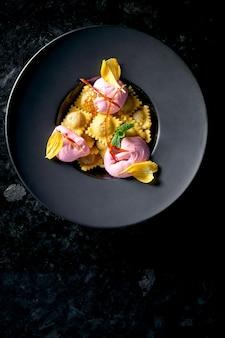 Сладкие равиоли с вишней и розовым мороженым подаются в черной тарелке на темном мраморном столе. ресторанная еда. итальянская кухня. вареники со сладкой начинкой