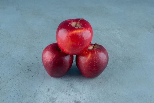 Сладкие красные яблоки на мраморном фоне. фото высокого качества