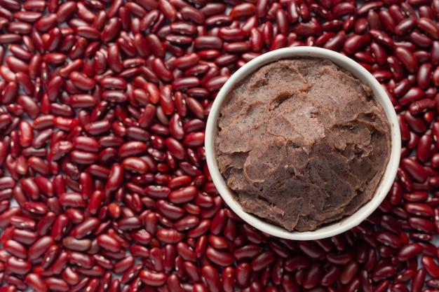 Dolce pasta di fagioli rossi in una ciotola bianca posto sul pavimento tra i semi di fagioli rossi