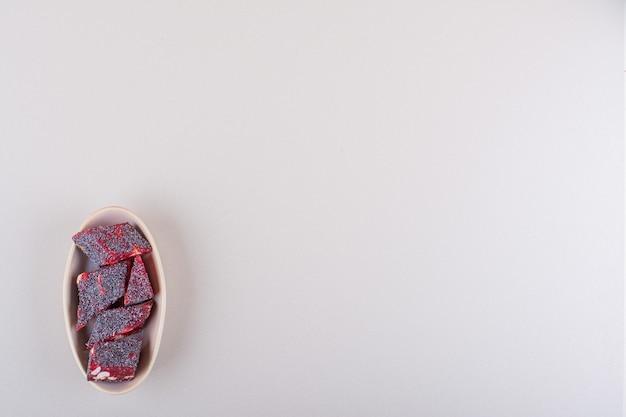 Caramelle rosse dolci con i dadi in ciotola beige su fondo bianco. foto di alta qualità