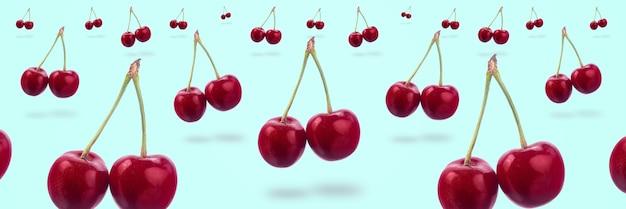 Sweet red cherry levitating, over azure background, panoramic image