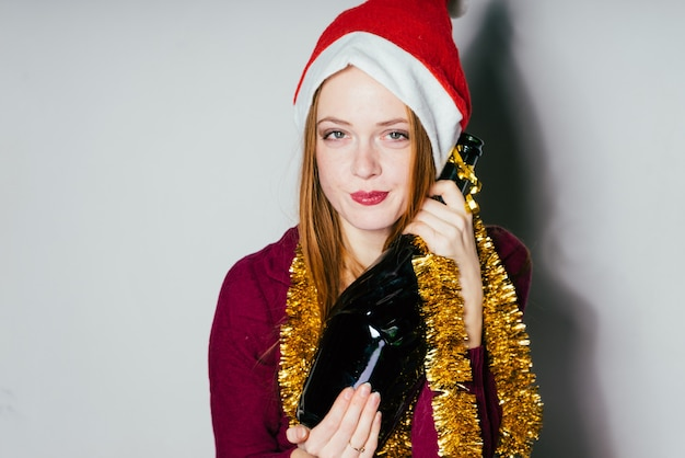 Милая рыжеволосая девушка в красной шапочке, как дед мороз, встречает новый год, держит бутылку шампанского
