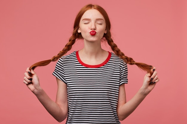 Sweet red-haired girl with red lips sends air kiss with closed eyes holding two braids in hands dressed in stripped t-shirt, flirting isolated