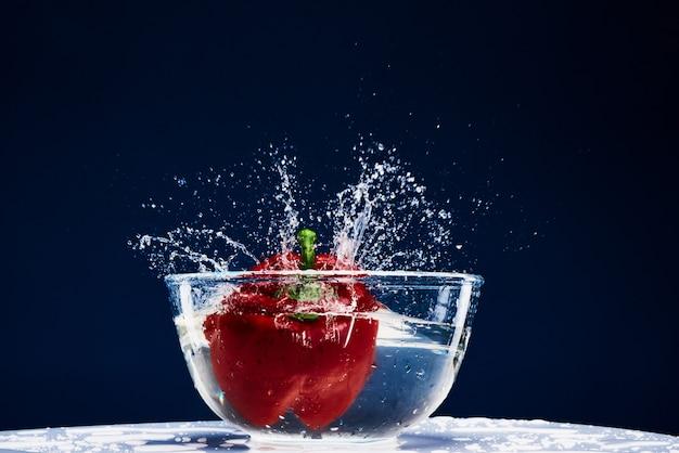 Sweet red paprika in water splash pepper in glass.