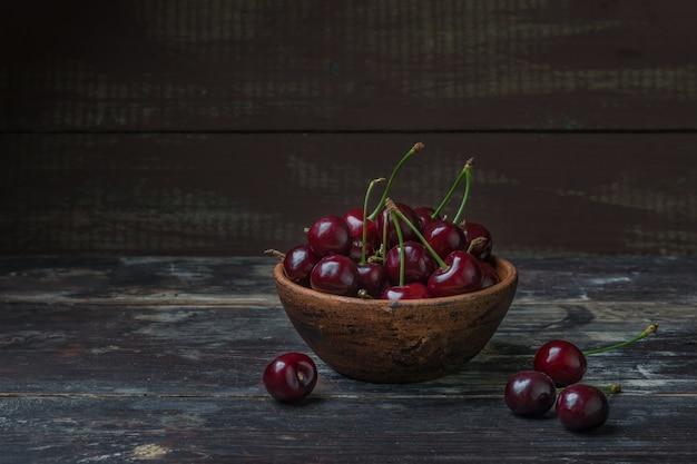 Сладкая спелая вишня. свежая вишня в миске на деревянных фоне. изобилие сельского хозяйства