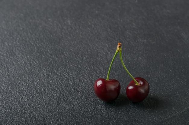 Сладкая спелая вишня. свежая вишня на черном фоне. изобилие сельского хозяйства