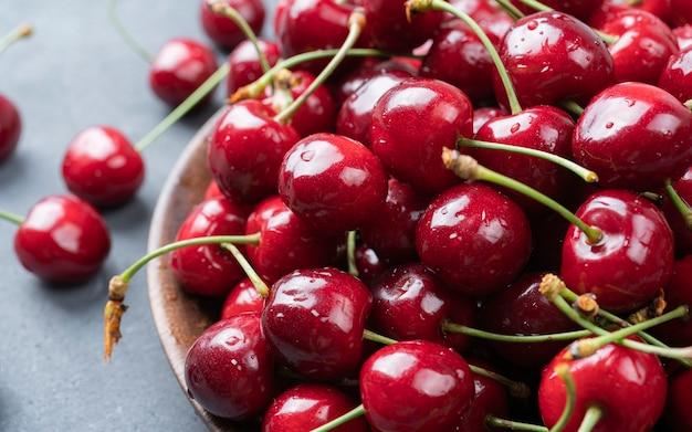 탁자 위의 나무 그릇에 달콤한 익은 체리 어두운 배경 매크로에 있는 아름다운 육즙 열매 매크로