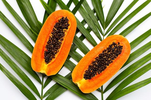 Сладкая спелая папайя на тропических пальмовых листьев. вид сверху