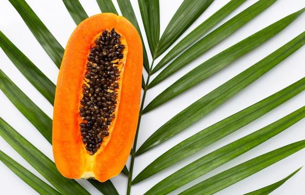 Сладкая спелая папайя на тропических пальмовых листьев.