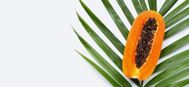 Sweet ripe papaya on tropical palm leaves. top view