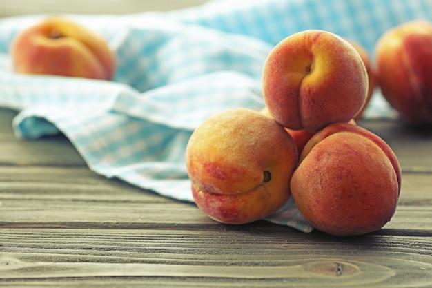 Сладкие спелые персики на столе крупным планом Premium Фотографии