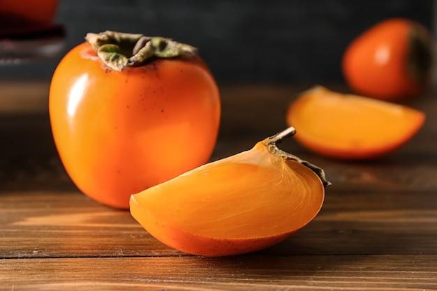 木製のテーブルの上の甘い熟した柿