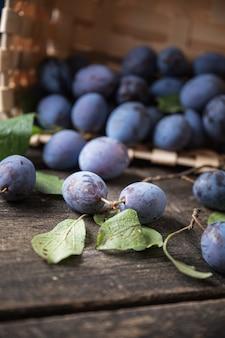 かごから木の表面に散らばる甘い熟した紫色のプラム。