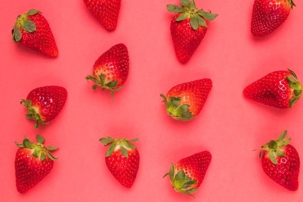 ピンクの背景に甘い熟したイチゴ