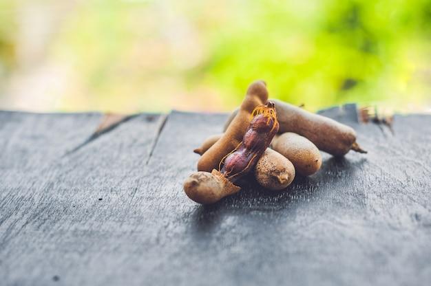 木製の背景に甘い熟したタマリンドポッド