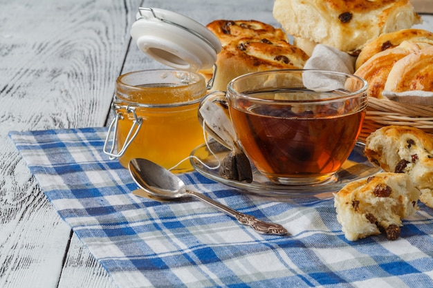 レーズンと紅茶のカップと甘いロールパン