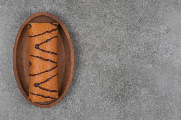 Sweet roll cake on wooden plate