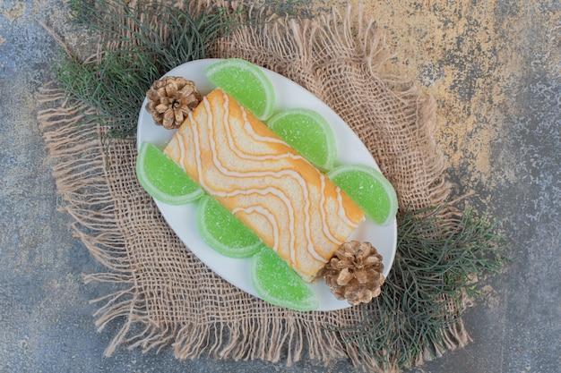 Rotolo dolce con marmellate e pigne verdi su un piatto bianco. foto di alta qualità