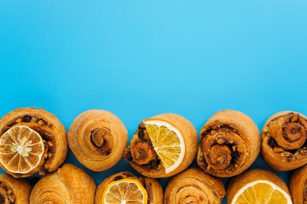 Сладкие булочки на синем фоне с копией пространства плоской планировки