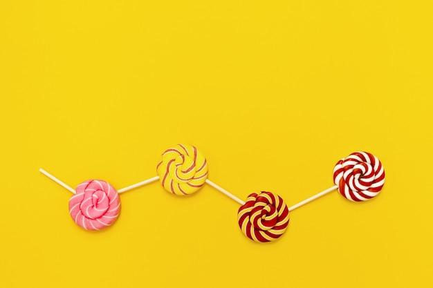 Сладкие круглые конфеты леденцы с полосками на палочке с копией пространства. креативная концепция натюрморт сладости на день рождения, вечеринка, праздники. вид сверху и плоская планировка.