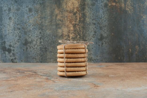 大理石の背景にロープで甘い丸いクッキー