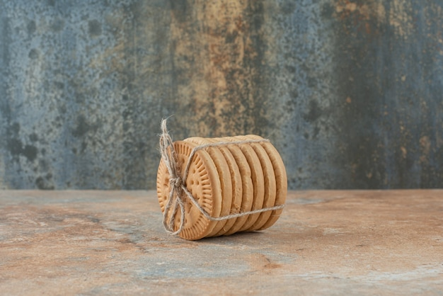 Sweet round cookies in rope on marble background