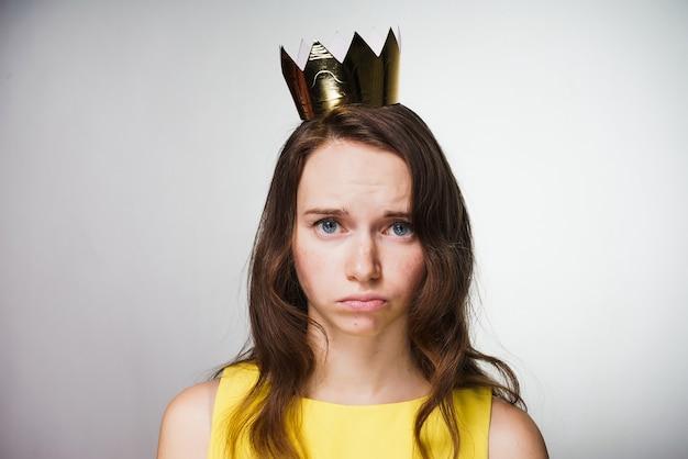 黄色いドレスを着た甘い悲しい少女は動揺し、彼女の頭には黄金の冠が贈り物を受け取らなかった