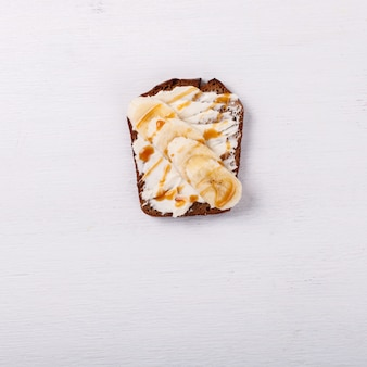 Sweet sandwich with cream-cheese and banana with caramel