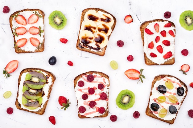 Sweet sandwiches with cream cheese and fresh berries and fruit on white background
