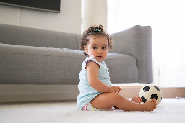 Sweet serious black haired baby girl in pale blue clothes sitting on floor with soccer ball, a. side view. kid at home and childhood concept