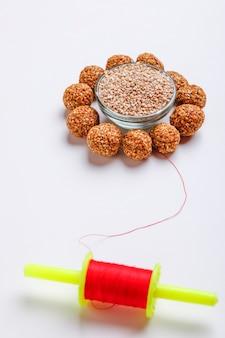 Sweet sesame laddu and sesame seed in glass bowl with fikri for indian festival makar sankranti