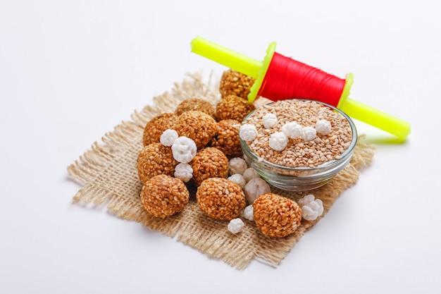 Sweet sesame laddu and sesame seed in glass bowl with firki