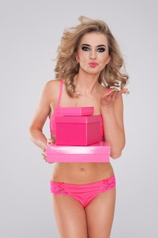 Donna dolce e sexy in biancheria che dà i regali rosa