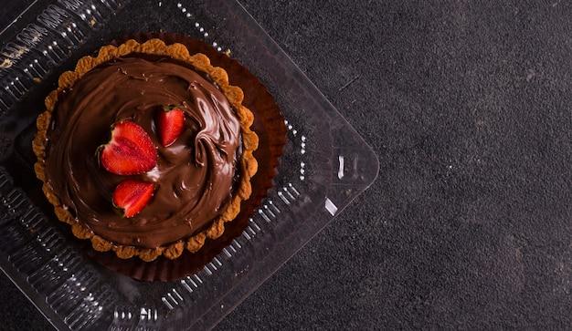 달콤한 가게 개념입니다. 검정색 배경에 있는 상자에 초콜릿 타르트. 복사 공간