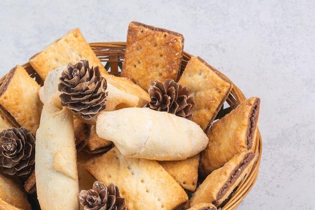 Сладкое песочное печенье и шишка в корзине, на мраморе.