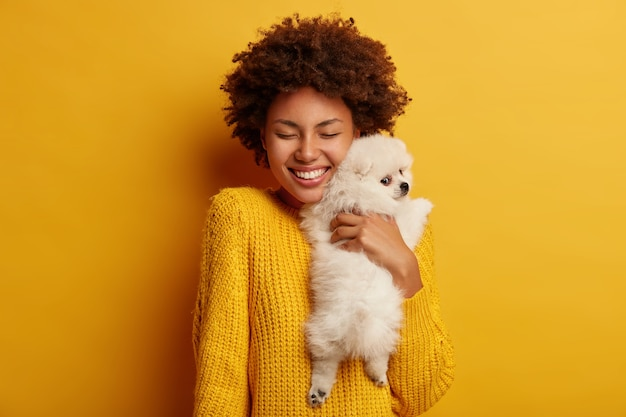 Sweet shot of cheerful afro woman embraces with big love her spitz dog