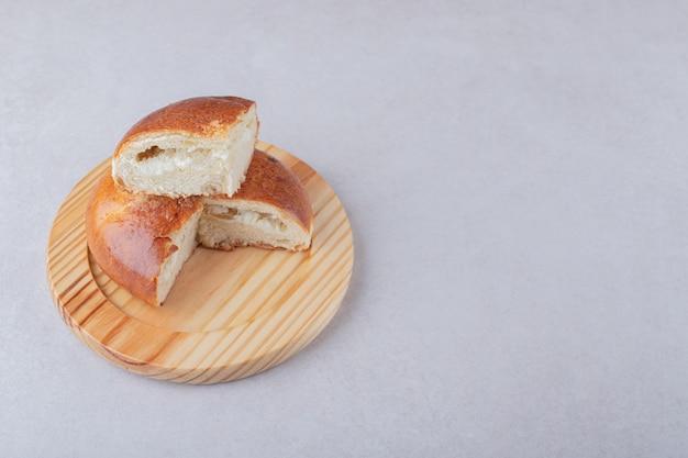 大理石のテーブルの上の木の板の甘いスライスされたパン。
