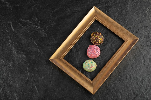 Piccole ciambelle dolci con granelli su un tavolo nero.