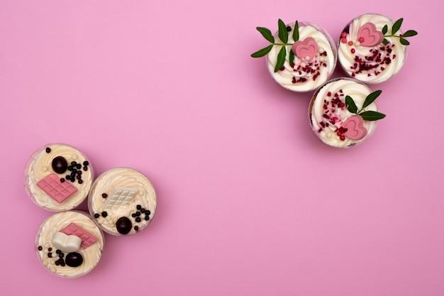 커스터드, 초콜릿, 견과류 및 과일과 장식 및 크림 치즈로 만든 달콤한 작은 수제 사소한 디저트. 분홍색 배경 복사 공간에 평평하게