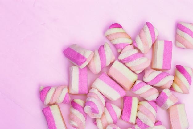 ピンクの背景に甘い小さなマシュマロ