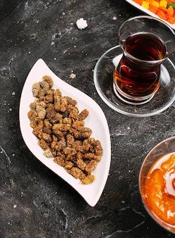 Sweet small susam candies in white plate with peach confiture and turkish tea.