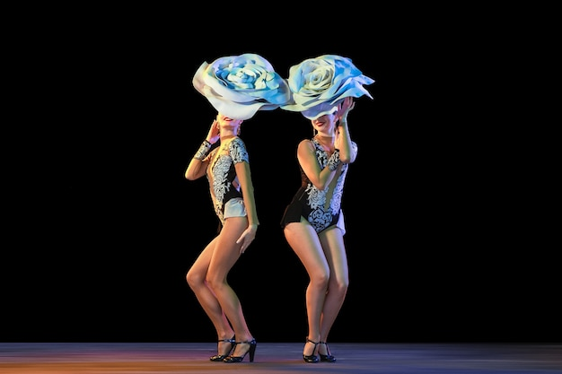 Sweet smell. young female dancers with huge floral hats in neon light on black wall.