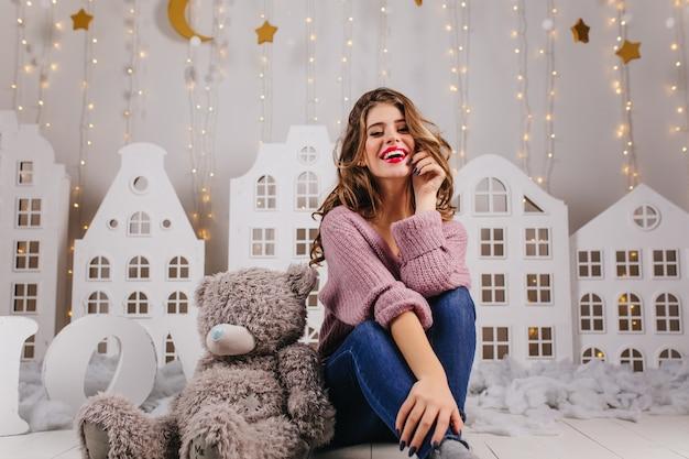 Милая, улыбающаяся, молодая девушка в уютном кресле сидит на полу с плюшевым мишкой