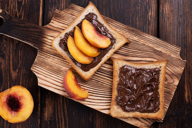 甘いスナック、暗い木製の背景、上面図のまな板の上のプレートに桃のスライスとチョコレートペーストトースト。