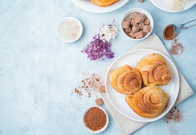 Сладкие булочки улиток с какао и сахаром и цветами на голубом фоне.